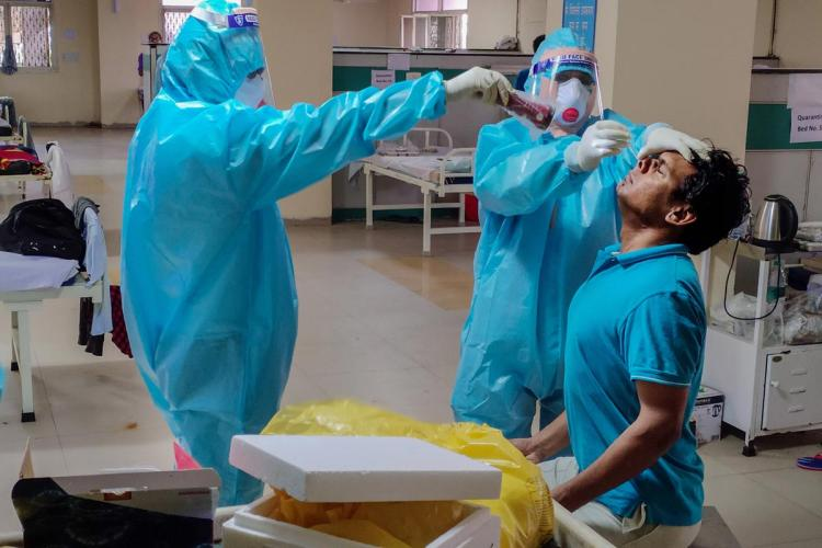 Swab test of man being taken by two people in blue PPE