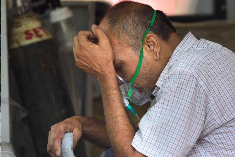 Man with inhaler mask on his face sits with hand on head