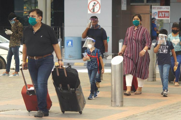 Passengers walking with luggage outside an airport