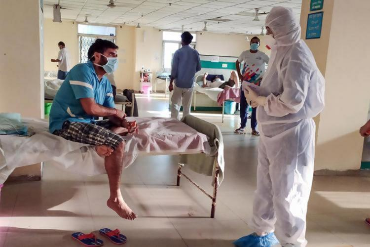 A man in blue t shirt and shorts sits on a hospital bed as a health workers in PPE kit talks to him