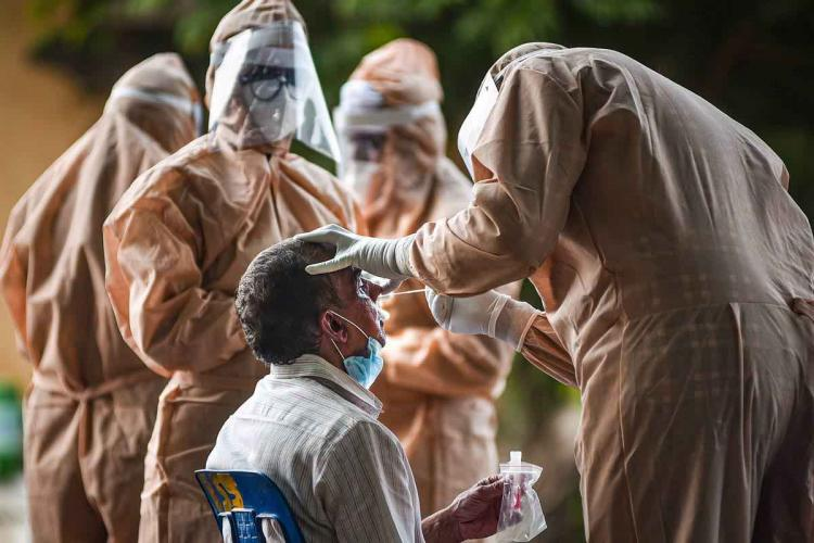 Man being tested by health workers in beige hazmat suits for coronavirus infection