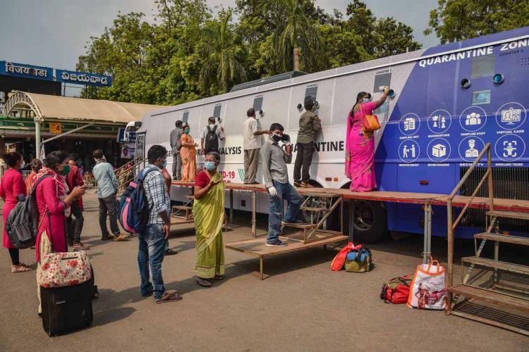 People queued up in front of a mobile COVID sample collection centre in front of the Vijayawada railway station
