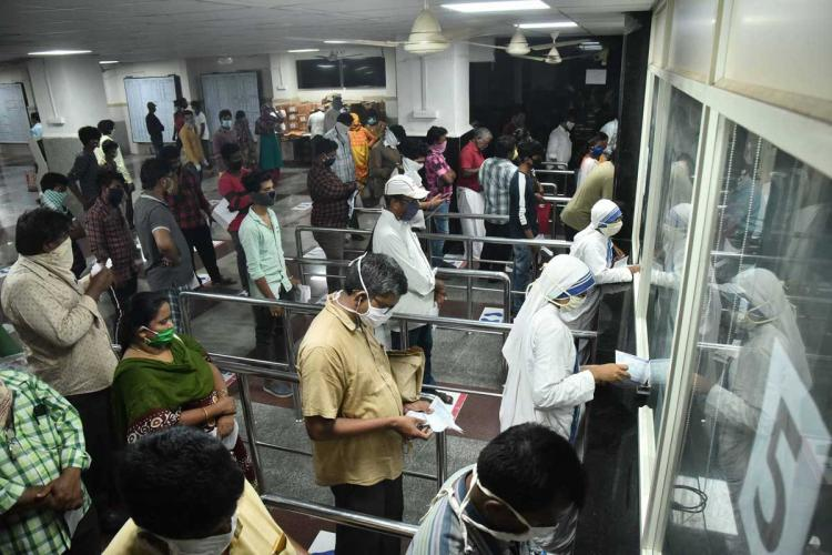 People standing in queues at counters in Vijayawada wearing masks and standing apart