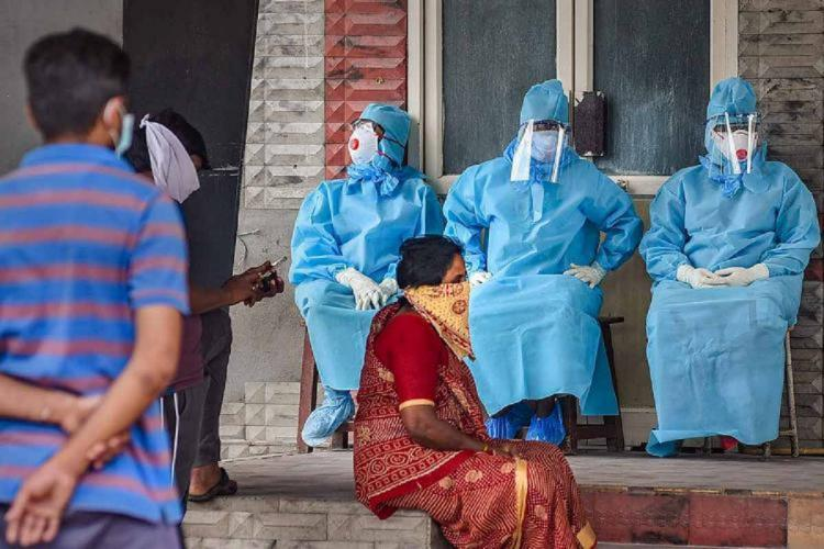 A woman sitting in front of three healthcare workers in PPE