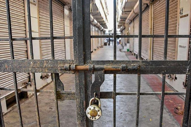 A bolted gate guarding several closed shutters of shops during the coronavirus lockdown in India