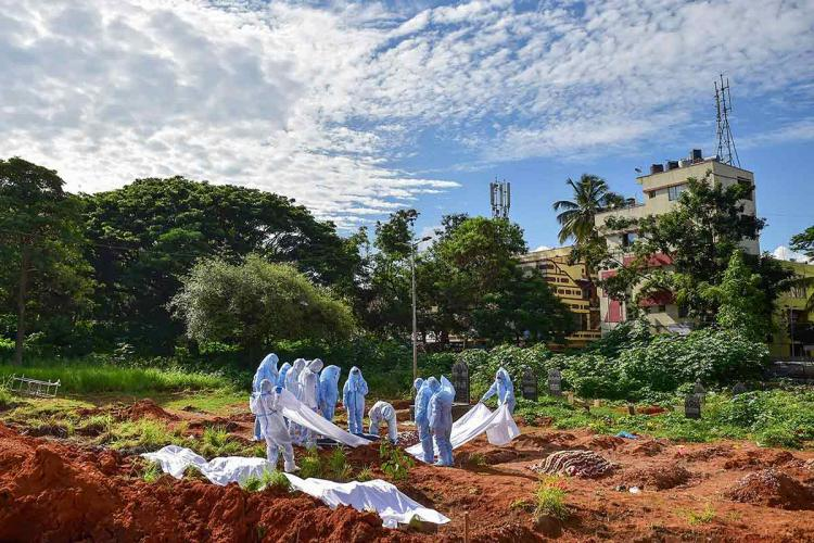 A group of workers wearing PPE prepare to bury the body of a COVID-19 victim in Bengaluru