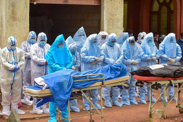 A group of healthcare workers in Bengaluru wearing PPE stand before bodies of covid-19 victims placed in bags on a stretcher