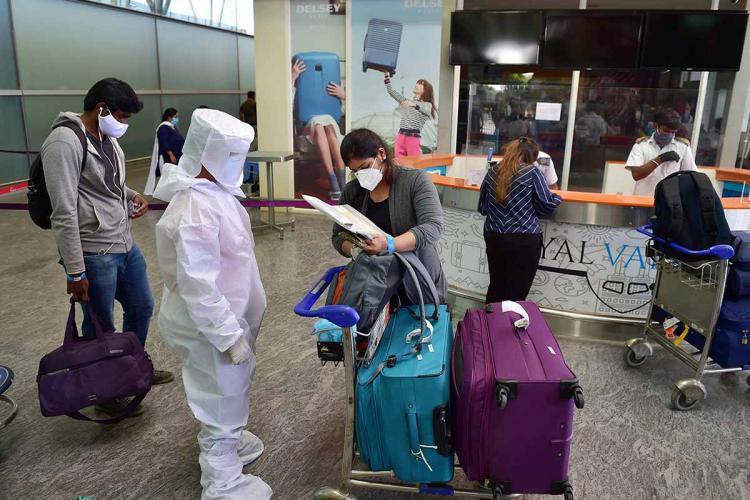 Staff with PPE kits were seen checking the passengers for details in an airport with masks