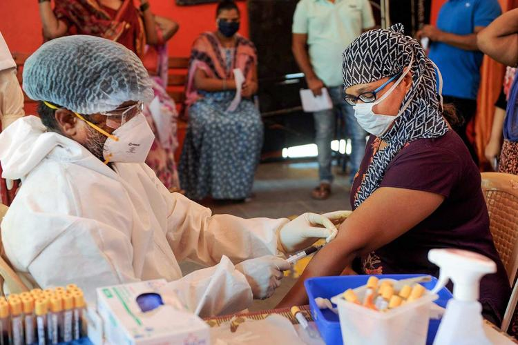 Health worker wearing PPE takes blood sample for coronavirus test for a woman in Mumbai