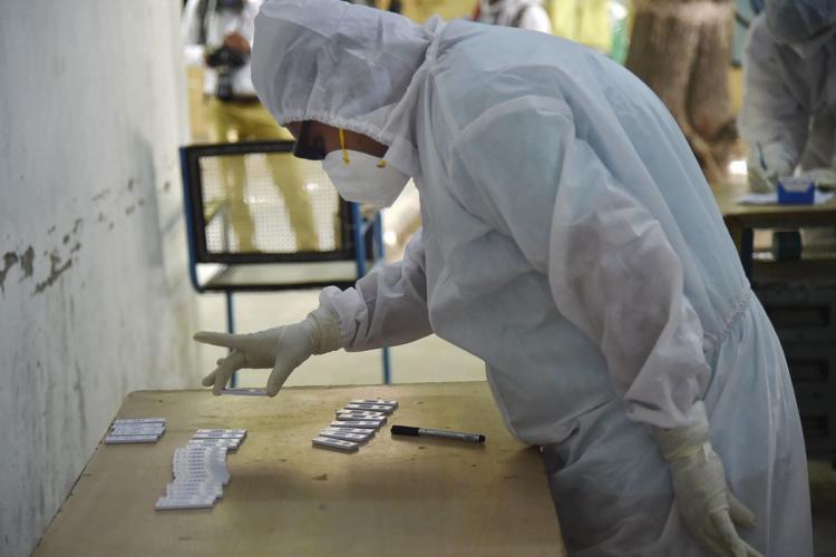 Health worker looks at coronavirus testing kits kept on a table
