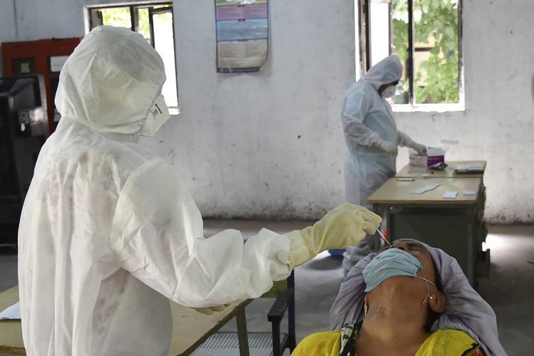 Medical personnel in PPE administers a swab test for COVID-19 on a woman