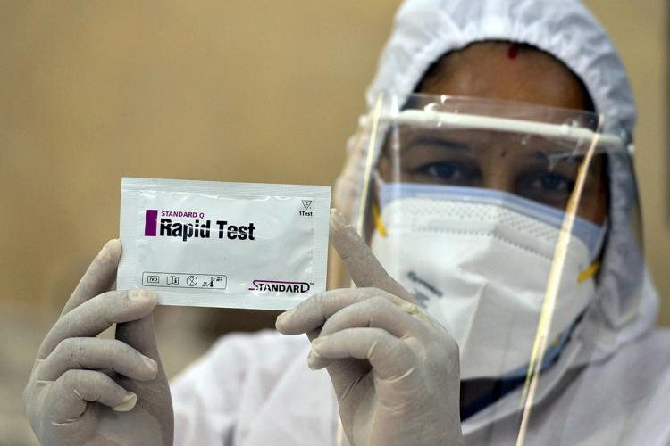 Healthworker holds up a COVID rapid test while wearing PPE