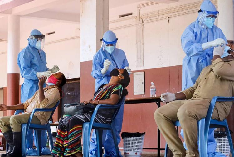 Three health worker in PPE suit collecting nasal swab sample from two woman and a men for coronavirus test