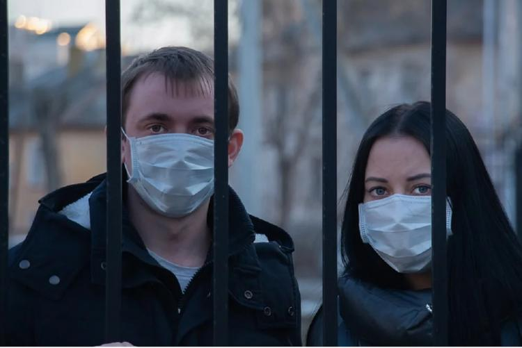Man and woman with mask standing behind a grill