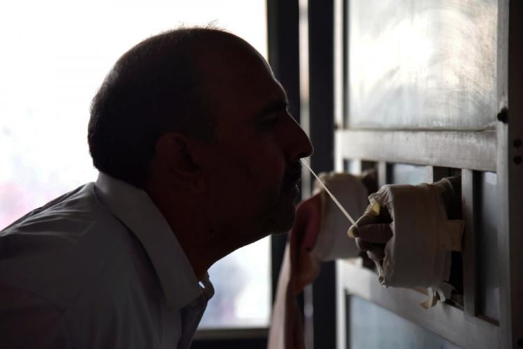 A man submitting his nasal sample for a COVID-19 test