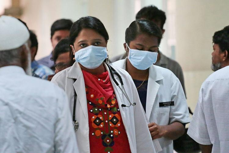 Two women doctors seen in medical coats and masks among some patients