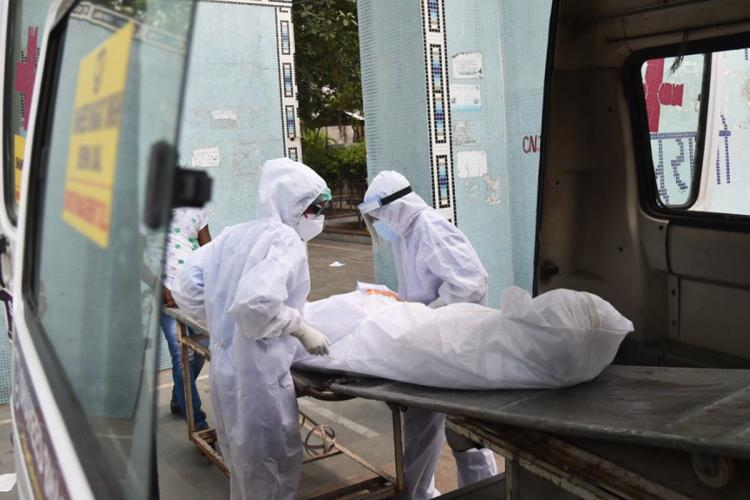 Two people in full white ppe suits putting a body wrapped in white in an ambulance