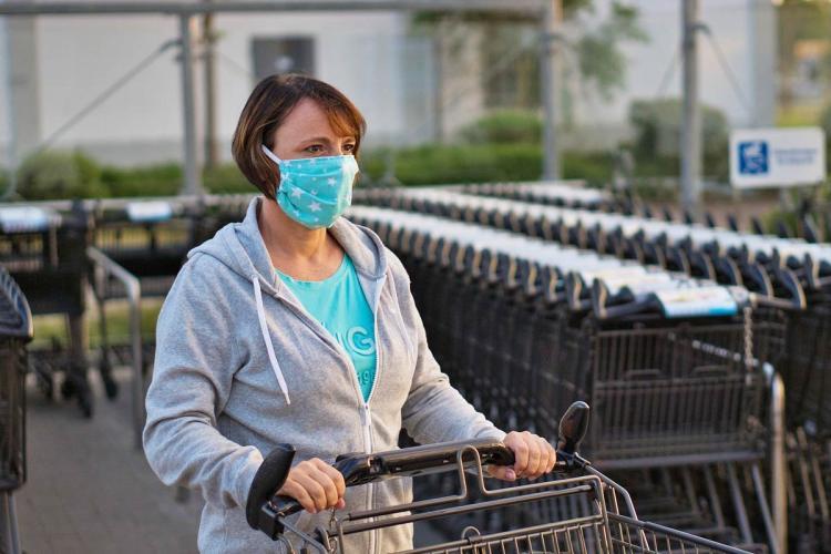 A woman wearing a mask pushes a shopping cart