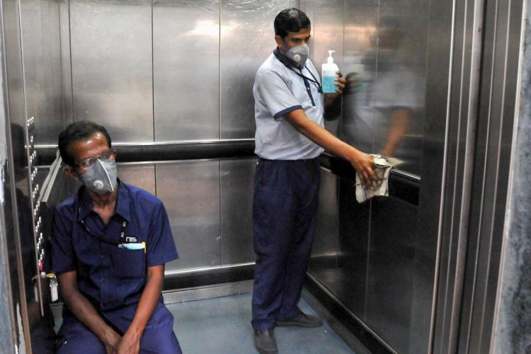 Man wiping lift inside a building with alcohol-based sanitiser