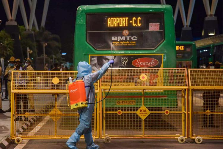 A man in PPE suit is sanitising a bus in Bengaluru which stands on the other side of a barricade