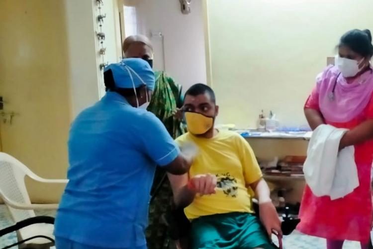A boy getting vaccinated at home by a team from the corporation