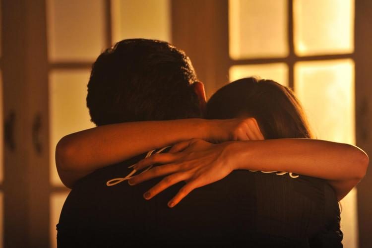Man and woman hugging with mans back facing camera and womans hands around his neck