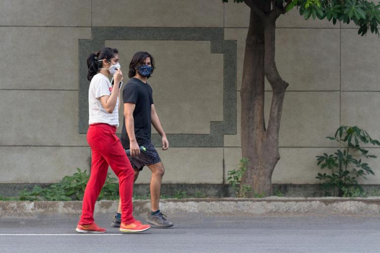A woman in a ponytail and mask wearing white shirt and red pants walking with a man with mask in black shirt and shorts on a road