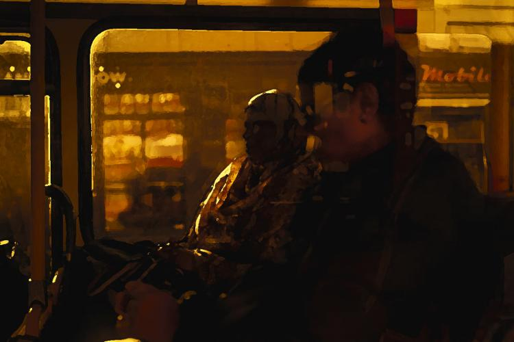 A representative picture of the silhouettes of a couple sitting inside a bus