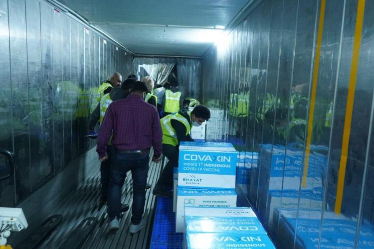Men moving boxes of the Covaxin vaccine