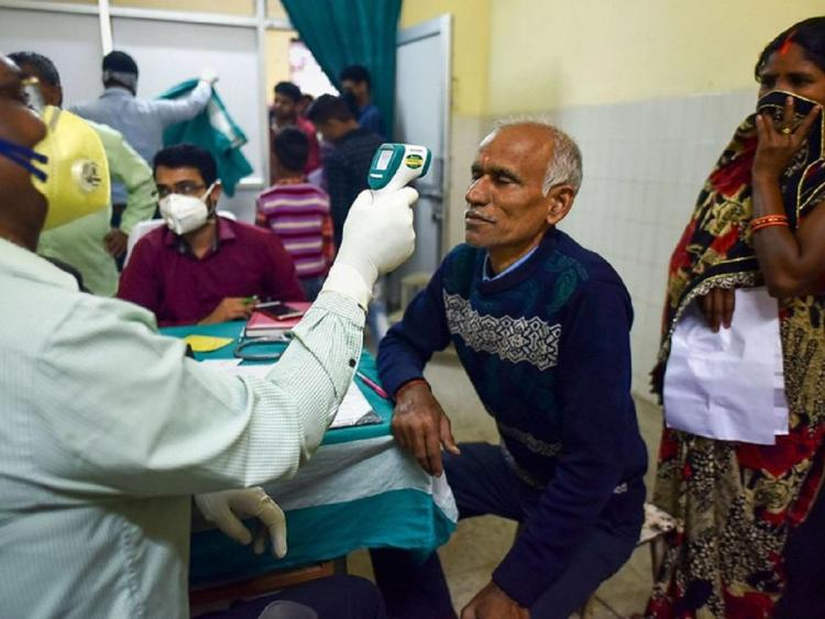 A medic conducts screening of an elderly patient in the wake for novel coronavirus
