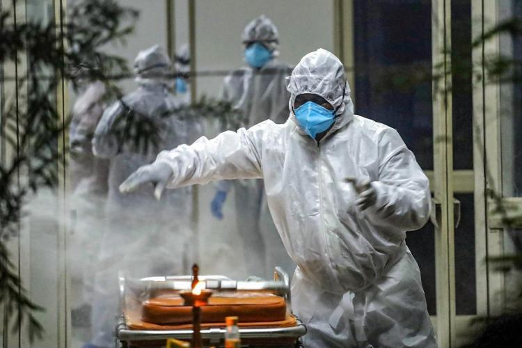 A health worker in white PPE kit and blue mask is seen around some smoke as other health workers are in the background