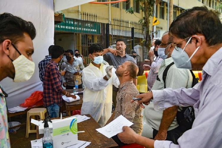 A health worker wearing mask and gloves collecting nasal swab from a man for coronavirus test
