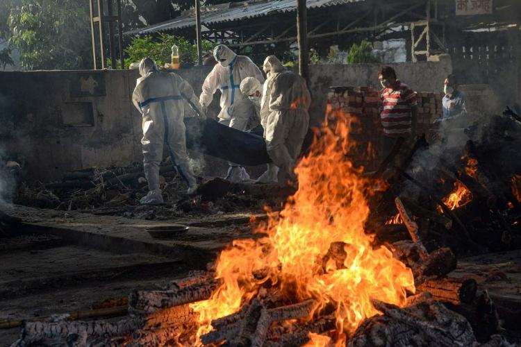 A funeral pyre and a number of people in PPE kits