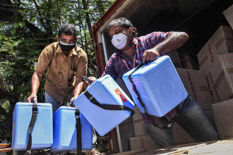Two men carry blue boxes of Covid-19 vaccine out of a truck