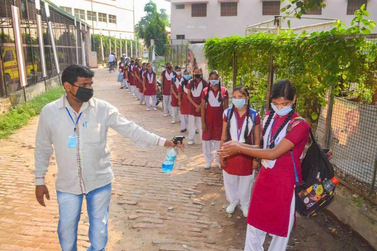 School girls in maroon and white uniform of salwar kameez standing in a long line with distancing and masks as a man sprays sanitiser in their hands one by one