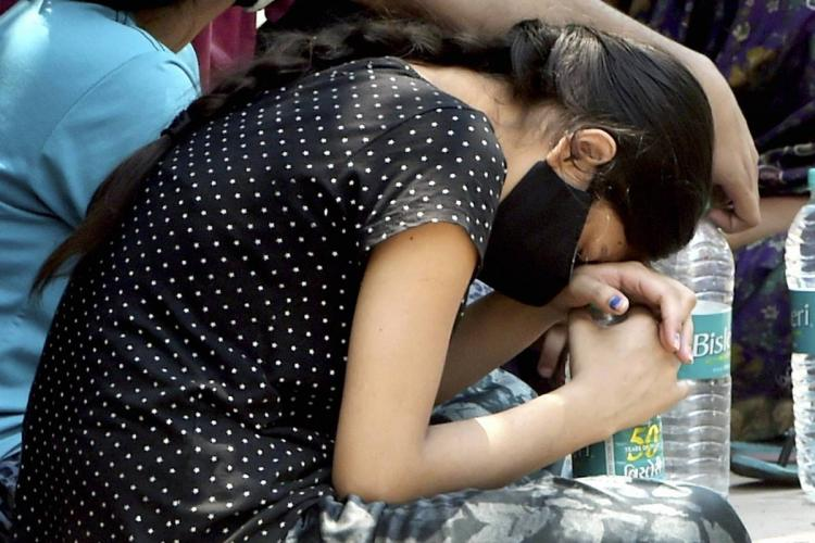 A young woman mourns the death of a relative due to Covid in Delhi