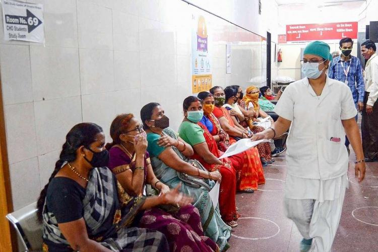 A number of women in Saris sit against a side wall as a nurse in white uniform passes them by