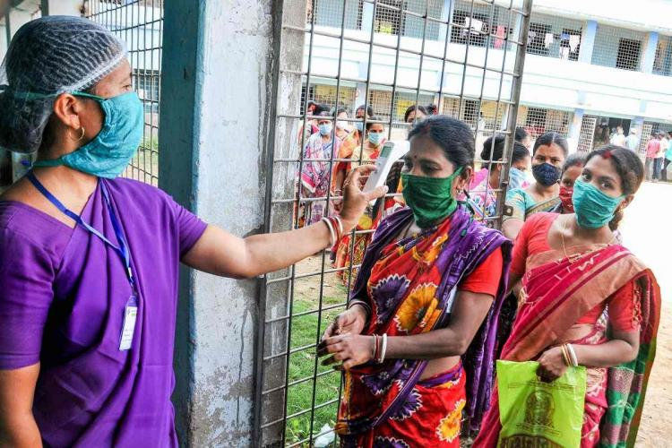 A woman in a violet sari and head cover and mask does thermal scanning of a number of women standing in queue to vote