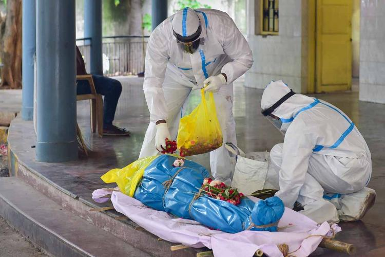 Two health workers in PPE placing flowers on deceased COVID-19 victims body