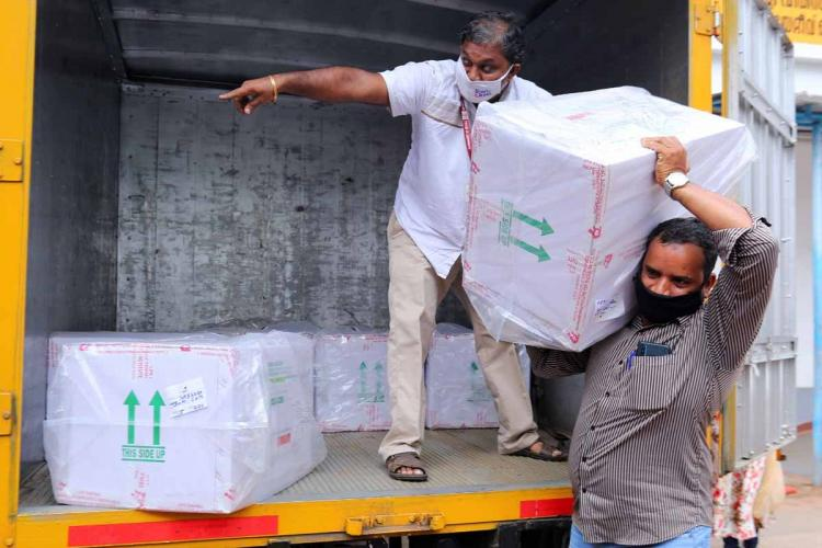 Officials transporting covid vaccine consignment after it reached kochi airport