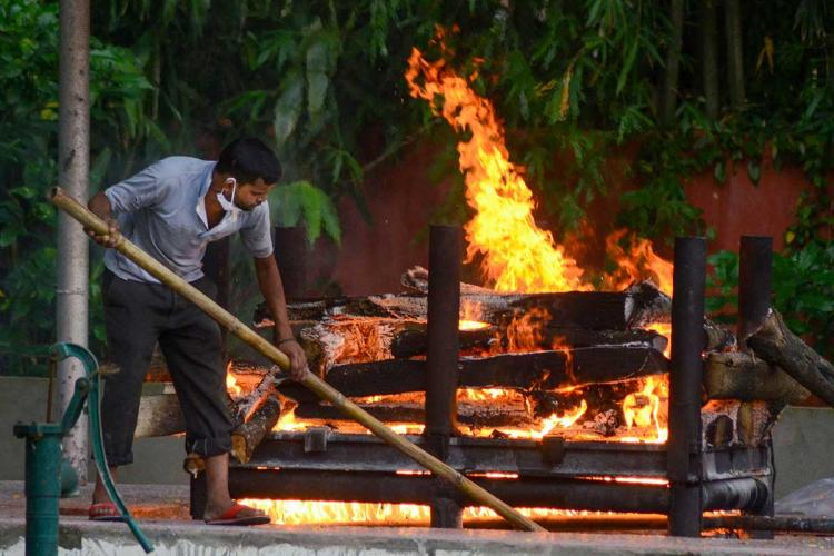 A man wearing a mask on his chin is seen moving the logs of a pyre where a body is burning