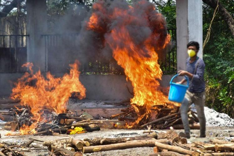 Two funeral pyres seen burning as a staff member walks by with a bucket in his hand