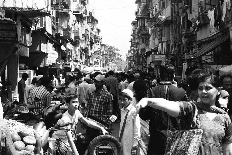 People crowd in a narrow street without masks