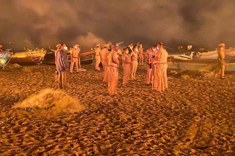 Group of policemen stand as fire rages on behind them in a fishing hamlet in Tamil Nadus Cuddalore district