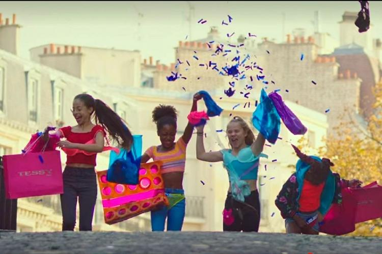 Still from Cuties on Netflix with the girls throwing their shopping in the air