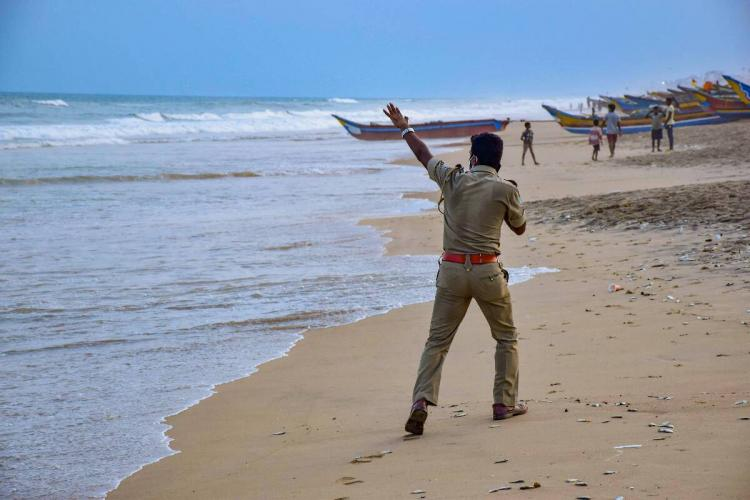 A police officer raises his left hand asking people to evacuate along the beach