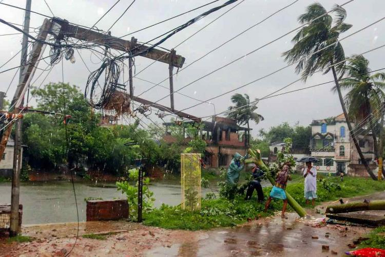 Workers try to restore a power line after a tree fell on it during a storm due Cyclone Amphan in Burdwan district of West Bengal