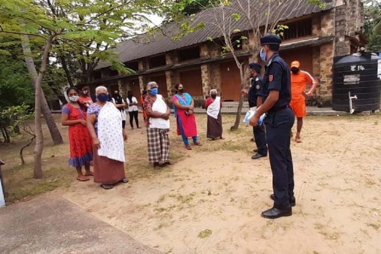 A few women at a coastal area listen to two men in black uniform
