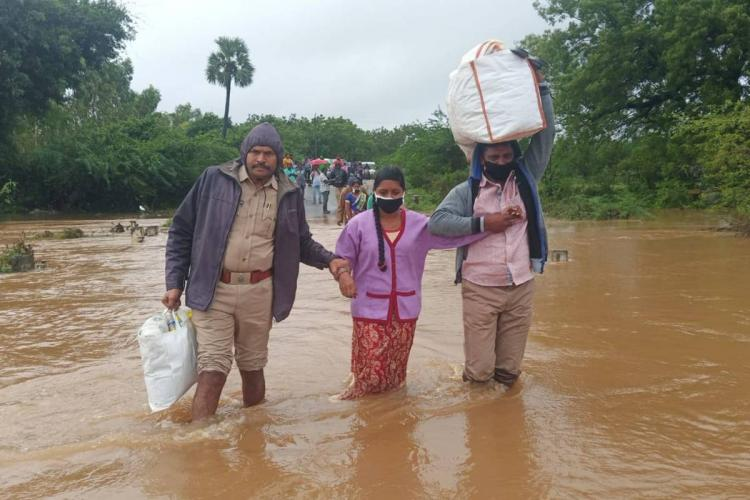 Nellore police helping a woman and man cross a flooded road