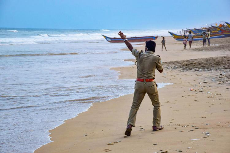 A coast guard on a beach alerting people about cyclone Yass